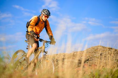 Cyclist Riding the Bike on the Beautiful Autumn Mountain Trail