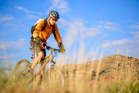 Cyclist Riding the Bike on the Beautiful Autumn Mountain Trail photo