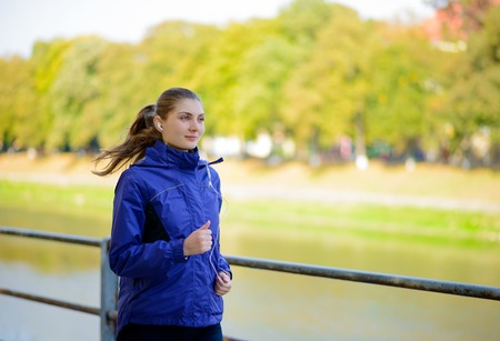 jog: Young Beautiful Woman Running in the Autumn Park. Active Lifestyle
