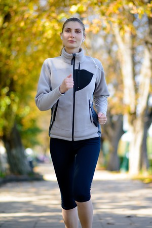 active lifestyle: Young Beautiful Woman Running in the Autumn Park. Active Lifestyle