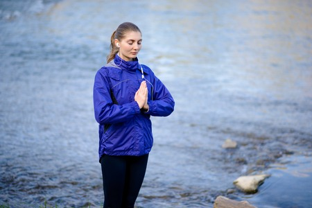 Young Beautiful Woman Meditate on the River. Active Lifestyle photo