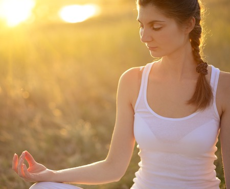 Young Beautiful Woman Practices Yoga on the Sunny Meadow. Active Lifestyle photo