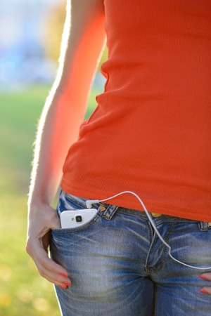 Smartphone with Headphones in Front Pocket of Woman Jeans photo