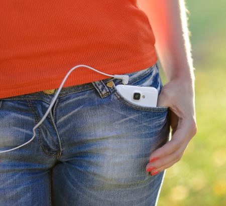 hands on pocket: Smartphone with Headphones in Front Pocket of Woman Jeans
