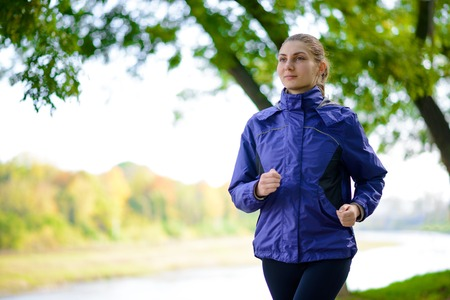 Young Beautiful Woman Running in the Autumn Park. Active Lifestyle photo
