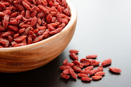 tibet bowls: Wooden Bowl Full of Dried Goji Berries on the Dark Table. Healthy Diet