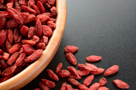 tibet bowls: Wooden Bowl Full of Dried Goji Berries on the Black Table. Healthy Diet