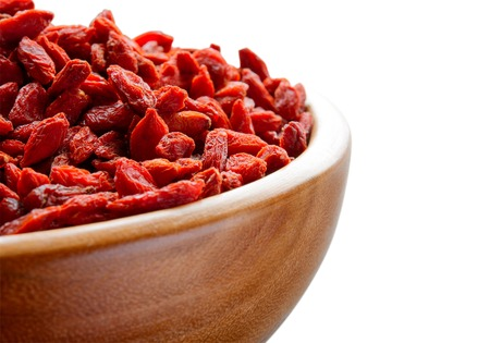 herbology: Wooden Bowl Full of Dried Goji Berries on the White Table. Healthy Diet