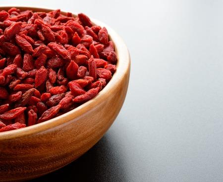 herbology: Wooden Bowl Full of Dried Goji Berries on the Dark Table. Healthy Diet
