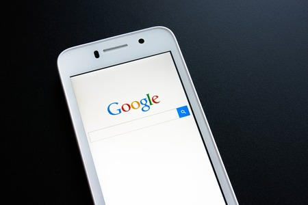 google: ZAPORIZHZHYA, UKRAINE - NOVEMBER 07, 2014: White Smart Phone with Google Search on Screen on the Black Table.