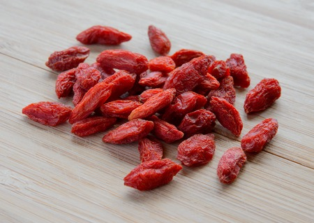herbology: Heap of Dry Goji Berries on the Wooden Table. Healthy Diet