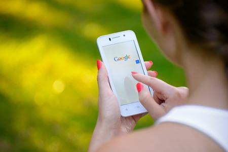 Zaporizhzhya, UCRÂNIA - 20 de setembro de 2014: Mulher nova que usa o Google Web Search em seu telefone esperto. Editorial