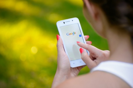 logo marketing: ZAPORIZHZHYA, UKRAINE - SEPTEMBER 20, 2014: Young Woman Using Google Web Search on her Smart Phone.