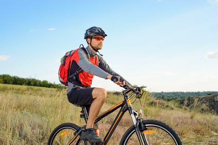 red sky: Cyclist Riding the Bike on the Beautiful Summer Mountain Trail. Sport Lifestyle Concept.
