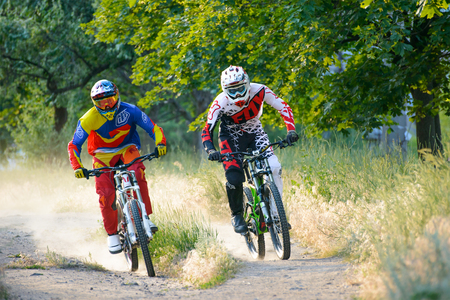 extreme sports: ZAPORIZHZHYA, UKRAINE - JUNE 16, 2015: Two Fully Equipped Professional Downhill Cyclists Riding Bikes on the Summer Trail. Extreme Sports