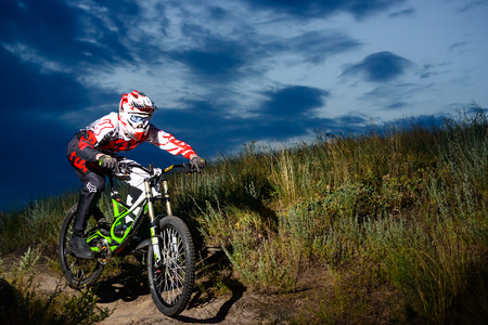extreme sports: ZAPORIZHZHYA, UKRAINE - JUNE 16, 2015: Fully Equipped Professional Downhill Cyclist Riding the Bike on the Night Rocky Trail. Extreme Sports