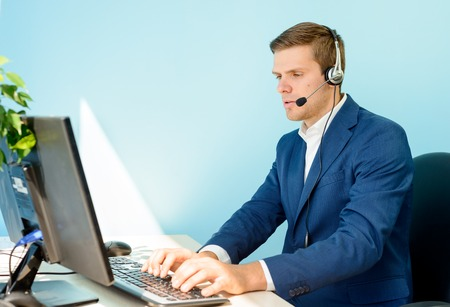 Jonge customer support telefoon operator met headset werken op computer in het kantoor.