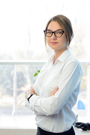 modern businesswoman: Young Attractive Smiling Businesswoman in White in the Bright Modern Office. Business Concept