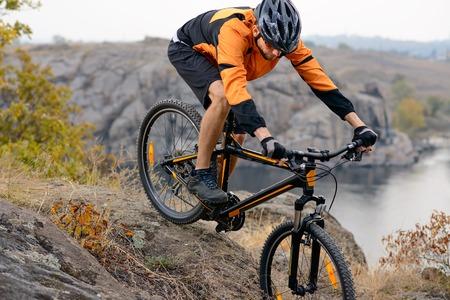オレンジのサイクリストを川の下の岩の丘を自転車に乗って着る。極端なスポーツのコンセプト。