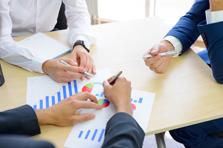 business results: Business People Analyzing Financial Results on Graphs around the Table in Bright Modern Office. Team Work Concept Stock Photo