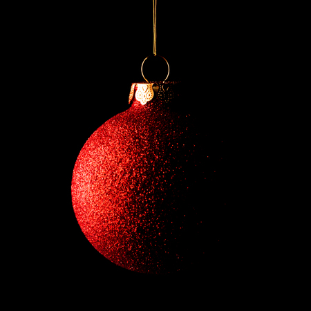 black and red: Red Christmas Ball on the Black Background. Greeting Card Stock Photo