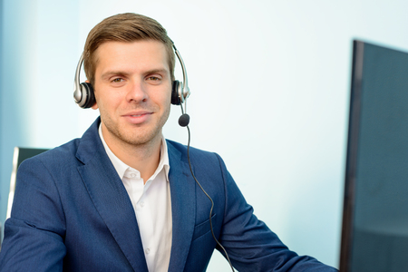 technical assistant: Young Customer Support Phone Operator with Headset at his Working Place in the Office.