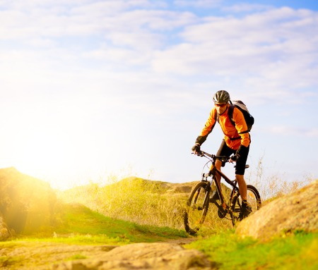 Cyclist Riding the Bike on the Morning Mountain Trail