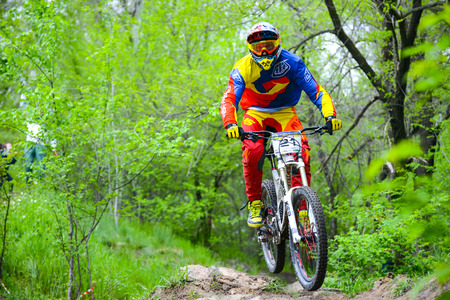 extreme sports: ZAPORIZHZHYA, UKRAINE - MAY 03, 2015: Professional DH Biker is Riding a Mountain Bike on the Trail of Khortytsya Island During the Iron Bridge Competition, a Stage of Downhill Ukrainian Cup. Extreme Sports Editorial