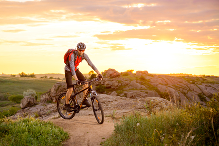bike trail: Cyclist Riding the Bike on the Mountain Rocky Trail at Sunset