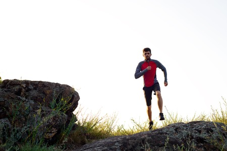 atleta corriendo: Young Sportsman Running on the Rocky Mountain Trail in the Evening. Active Lifestyle Concept Foto de archivo