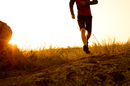 trails: Close-up of Sportsmans Legs Running on the Rocky Mountain Trail at Sunset. Active Lifestyle Concept Stock Photo