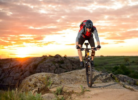 trails: Cyclist Riding the Bike Down Hill on the Mountain Rocky Trail at Sunset. Extreme Sports Stock Photo