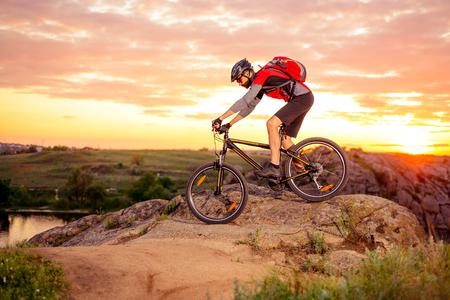 Radfahrer Riding the Bike Down Hill auf dem Berg Rocky Trail bei Sonnenuntergang. Extremsportarten Standard-Bild