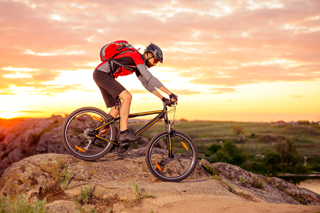 Cyclist Riding the Bike Down Hill on the Mountain Rocky Trail at Sunset. Extreme Sports Archivio Fotografico