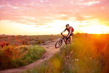 bike trail: Cyclist Riding the Bike on the Mountain Rocky Trail at Sunset. Extreme Sports Stock Photo