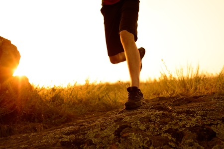 mountain sunset: Close-up of Sportsmans Legs Running on the Rocky Mountain Trail at Sunset. Active Lifestyle Concept Stock Photo