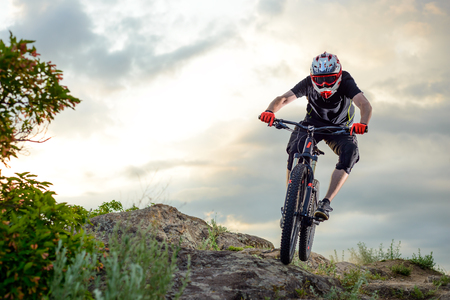 Professional Cyclist Riding the Bike Down Rocky Hill at Sunset. Extreme Sport Concept. Space for Text. Imagens - 66733507