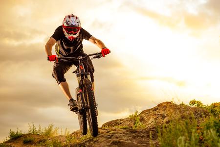 Professionele fietser rijden op de fiets Rocky Hill bij zonsondergang. Extreme sport concept. Ruimte voor tekst. Stockfoto