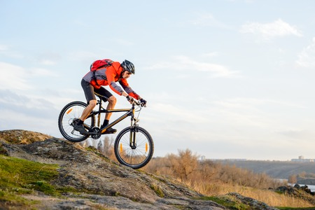 mountain biker: Cyclist in Red Jacket Riding the Bike Down Rocky Hill. Extreme Sport Concept. Space for Text.
