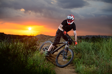 Professional Cyclist Riding the Bike on the Mountain Rocky Trail at Sunset. Extreme Sports Stock Photo