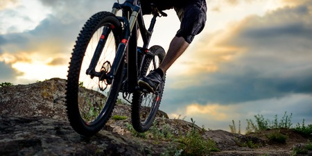 space for text: Cyclist Riding the Bike Down Rocky Hill at Sunset. Close up Extreme Sport Concept. Space for Text.