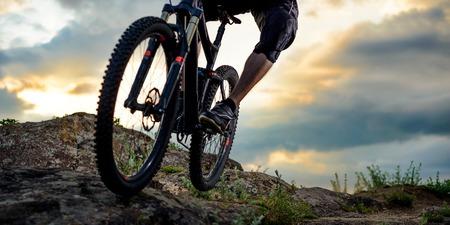 Fietser berijden van de fiets in Rocky Hill bij zonsondergang. Close-up Extreme Sport Concept. Ruimte voor tekst.