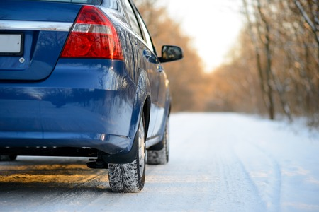 road surface: Blue Car with Winter Tires on the Snowy Road. Drive Safe Concept.