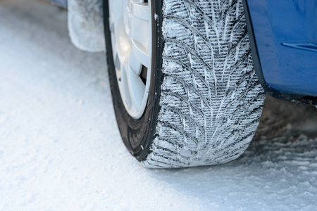 Close-up Image of Winter Car Wheel on the Snowy Road. Drive Safe Concept. Stock Photo