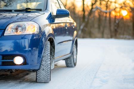 Blauwe auto met winterbanden op de sneeuwweg. Drive Safe Concept.