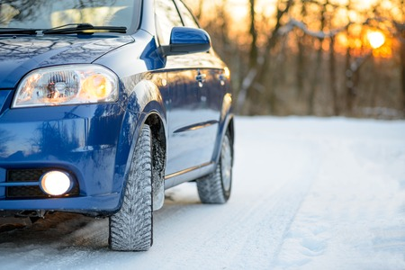 Blue Car with Winter Tires on the Snowy Road. Drive Safe Concept.