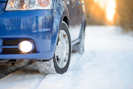 traction: Blue Car with Winter Tires on the Snowy Road. Drive Safe Concept.