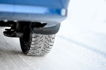 traction: Close-up Image of Winter Car Tire on the Snowy Road. Drive Safe Concept.