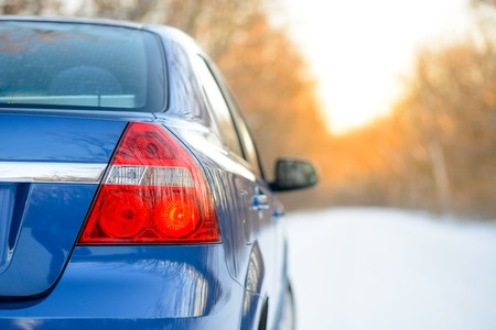 Blue Car on the Winter Snowy Road at Sunset. Close up Rear View. Travel and Safe Driving Concept.