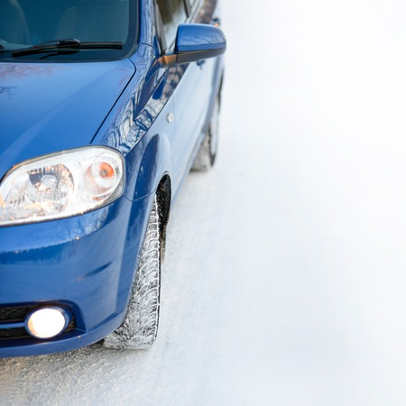 space weather tire: Blue Car with Winter Tires on the Snowy Road. Drive Safe Concept with Space for Text.